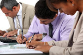 Business professionals filling in paperwork — Stock Photo