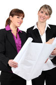 Two women holding plans — Stock Photo