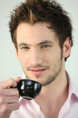 Young man drinking a cup of expresso — Stock Photo