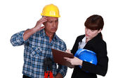 Confused tradesman watching an engineer writing on a clipboard — Stock Photo