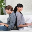 Couple sitting back to back on a sofa — Stock Photo