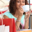 Woman enjoying coffee during shopping trip — Stock Photo