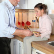 Granddad and granddaughter in the kitchen - Stock Photo