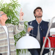 Man fixing ceiling light for old woman — Stock Photo