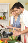 Coupe cooking in kitchen with cookbook — Stock Photo