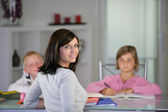 Mother helping her children with their homework — Stock Photo