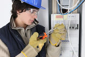 Young electrician working on a fuse box — Stock Photo