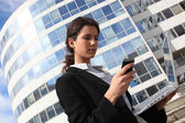 Brunette businesswoman stood outdoors with laptop and mobile — Stock Photo