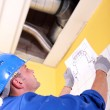 Stock Photo: Engineer examining ventilation system
