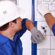 Foto Stock: Electrician watching plan