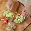 Man making salad in kitchen — Stock Photo #13832075