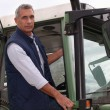 Farmer in the cab of his tractor - Stock Photo
