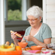 Senior woman eating on her terrace - Stock Photo