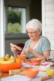 Senior woman eating on her terrace — Stock Photo