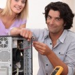 Woman watching her husband repair a computer — Stock Photo
