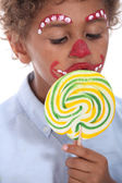 Little boy made-up sucking lollipop — Photo