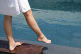 Woman dipping her foot in the swimming pool — Stock Photo