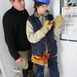 Stock Photo: Electrician and apprentice by fusebox