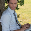 Relaxed executive using laptop in park — Stock fotografie