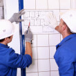 Two electricians inspecting electrical plan — 图库照片