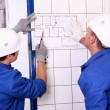 Two electricians inspecting electrical plan — Foto de Stock