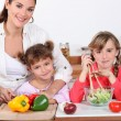 Mother and daughters making a salad. — Stock Photo
