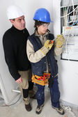 Electrician and apprentice by fusebox — Stock Photo