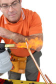 Plumber shaping copper pipe — Stock Photo