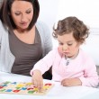 Mother and daughter completing a letter puzzle — Stock Photo