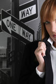 Businesswoman stood by sign posts — Stock Photo