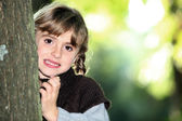 Young girl hiding behind a tree trunk — Stock Photo