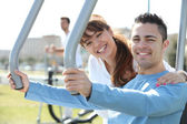 Smiling woman and man using fitness machines — Stock Photo