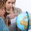 Mother and child looking at a globe — Stock Photo #14029973