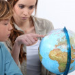 Mother and child looking at a globe — Stock Photo