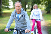 Senior couple riding bikes — Stockfoto