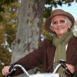 Old lady on a bike ride - Stock Photo