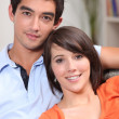 Stock Photo: Young couple sitting in their front room