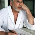 Older man doing a crossword — Stock Photo