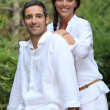 Stock Photo: Smiling couple wearing white in garden