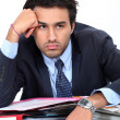 Bored businessman sat with pile of paperwork — Stock Photo #14034578