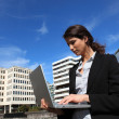 Young woman using a laptop outdoors in the city - Stock Photo