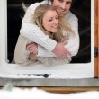 Couple hugging by chalet window — Stock Photo