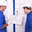Stock Photo: Electricians checking plan