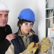 Electrician and his young apprentice — Stock Photo