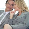 Business couple sharing a secret — Stock Photo