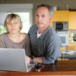 Married couple using laptop in the kitchen — Stock Photo #14039130