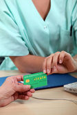 Health insurance card being passed from patient to medical staff — Stock Photo