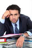 Gelangweilt geschäftsmann saß mit haufen papierkram — Stockfoto