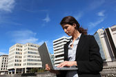 Young woman using a laptop outdoors in the city — Stock Photo