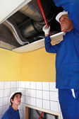 Two labourers checking ventilation system — Stock Photo